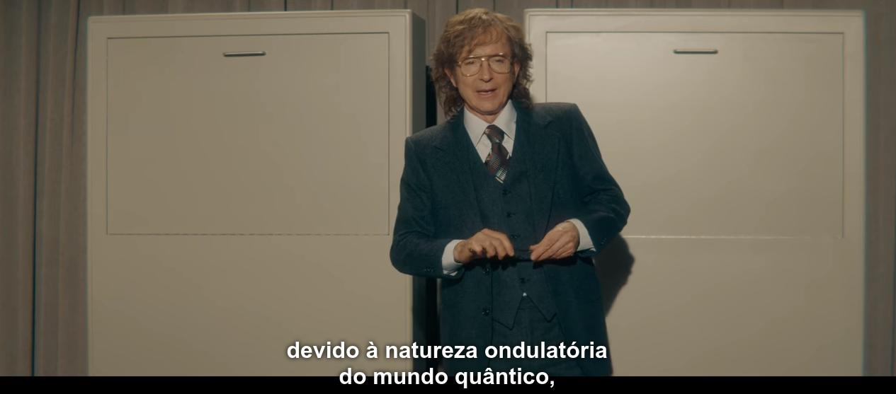 Cena de T03E07, com o Tannhaus do mundo original explicando o experimento do Gato de Schrödinger, dizendo: 'devido à natureza ondulatória do mundo quântico...'.