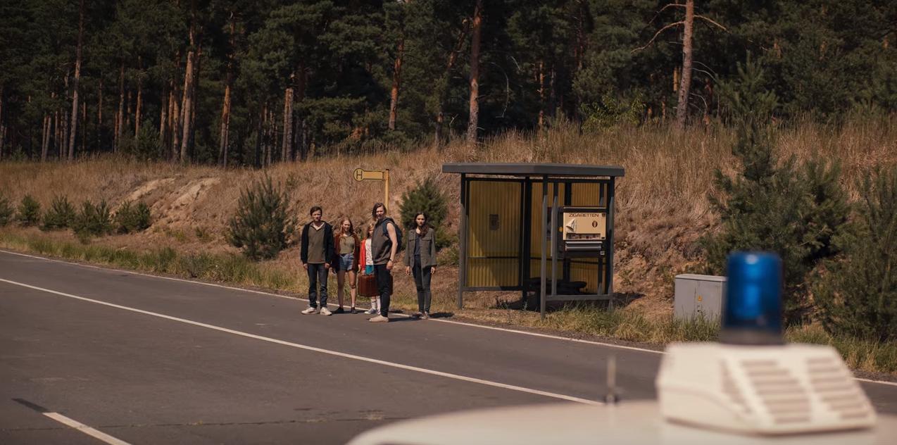 Cena de T02E05 em que Bartosz, Franziska, Elizabeth, Magnus e Martha descobrem que é possível viajar no tempo usando a máquina de Bartosz; na imagem, eles estão diante do ponto de ônibus, vendo passar os carros de polícia que levam um Ulrich idoso de volta à prisão-sanatório.