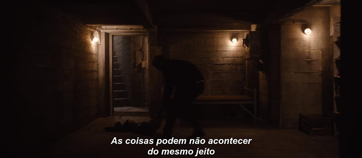 Ulrich arrastando o corpo de Helge para o bunker em cena do episódio T03E08, em que Claudia narra: 'As coisas podem não acontecer do mesmo jeito'.